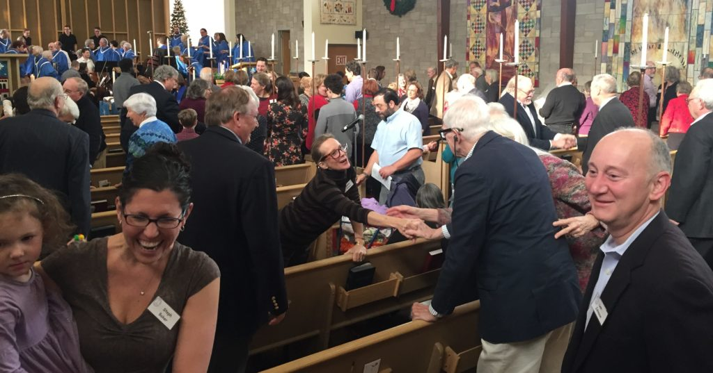 the congregation shaking hands and greeting each other across the pews