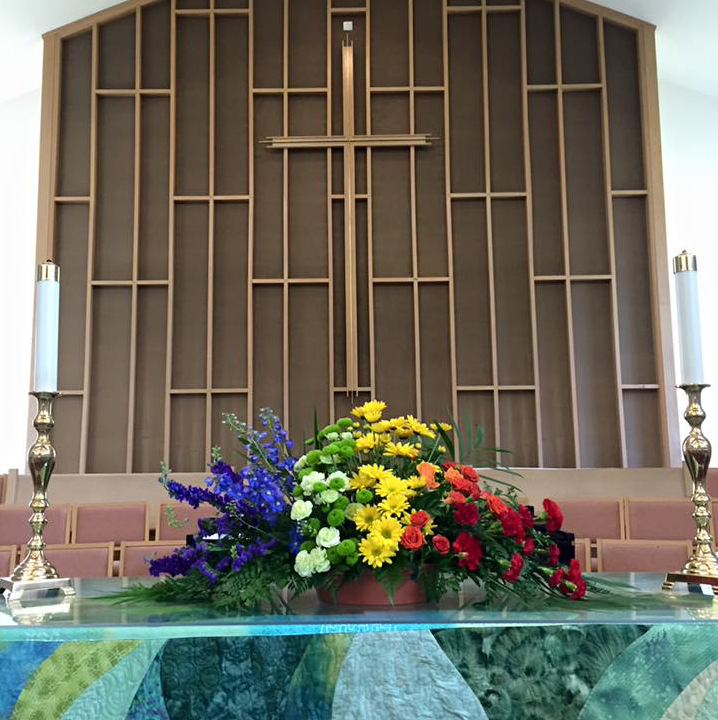 A rainbow bouquet of flowers on the altar in front of the cross