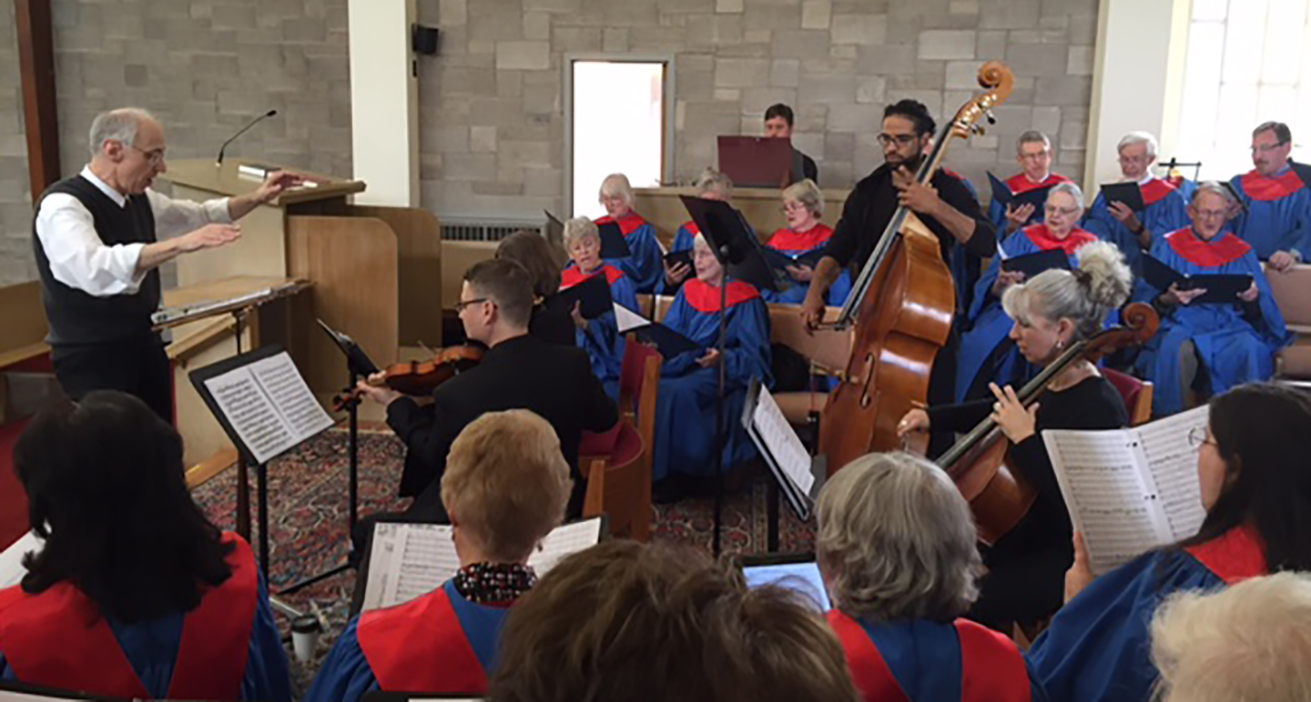 The choir, wearing red and blue robes, performing along with violin, cello, and bass players