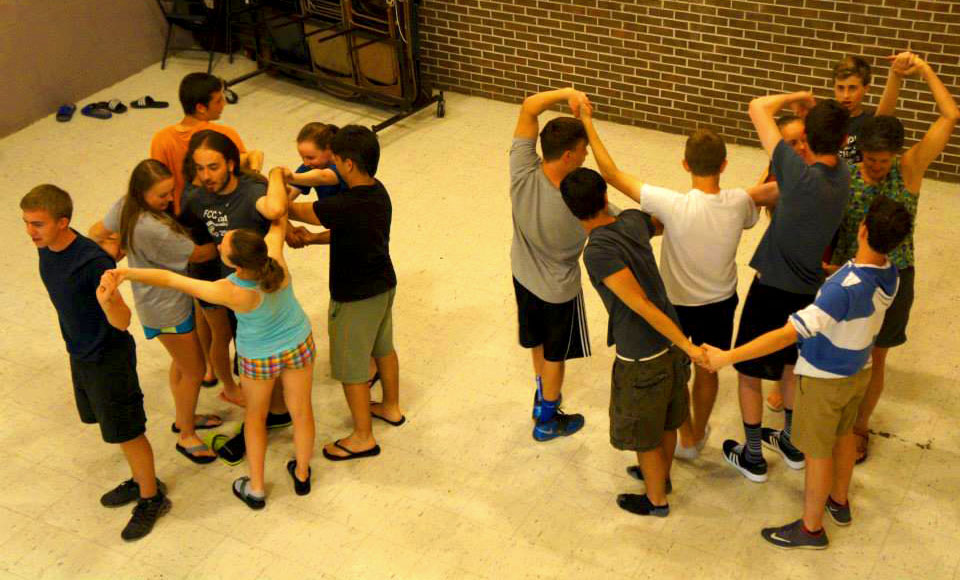 Two groups of 8 youth with their arms intertwined in a game or teambuilding exercise