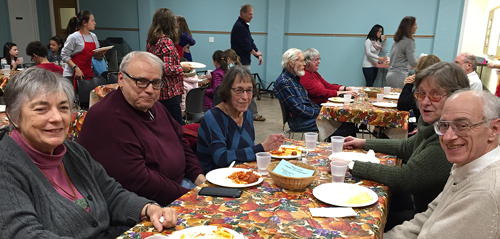 Several individuals around a table enjoying a churchwide meal in the fellowship hall