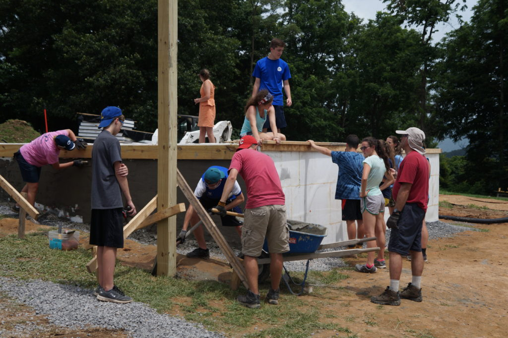 Eleven people working on various aspects of the foundation of a Habitat for Humanity home