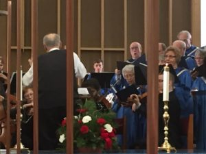 Bill Cowdery conducting the choir, dressed in blue, as viewed between candle posts