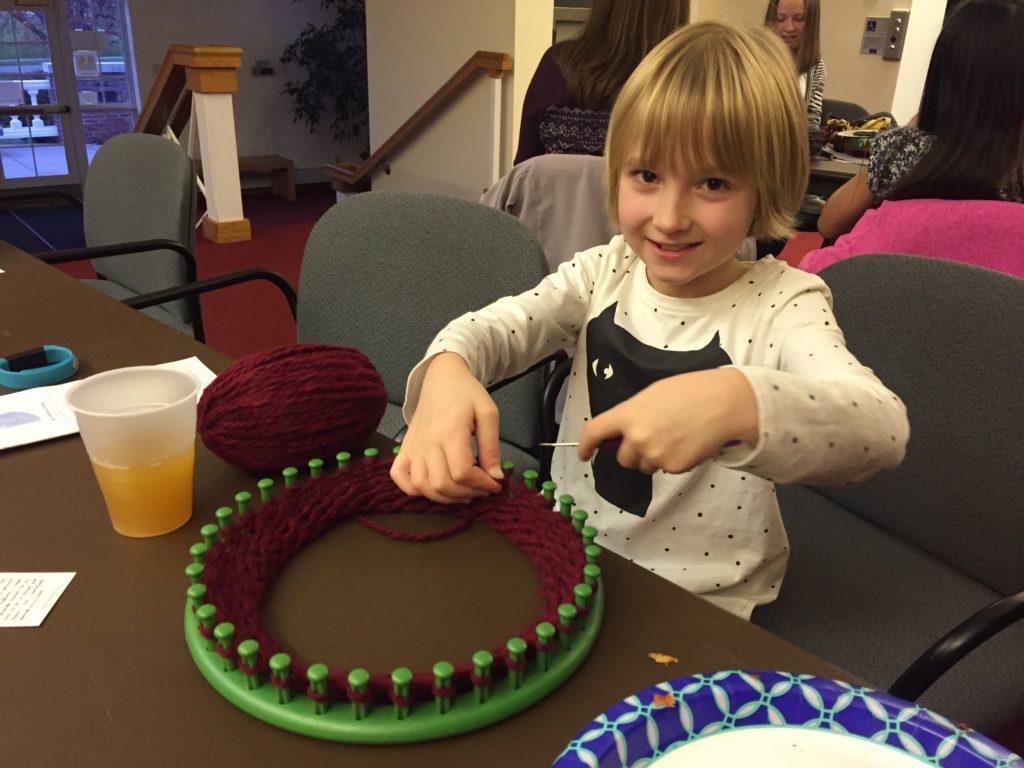A girl knitting with maroon yarn on a loom