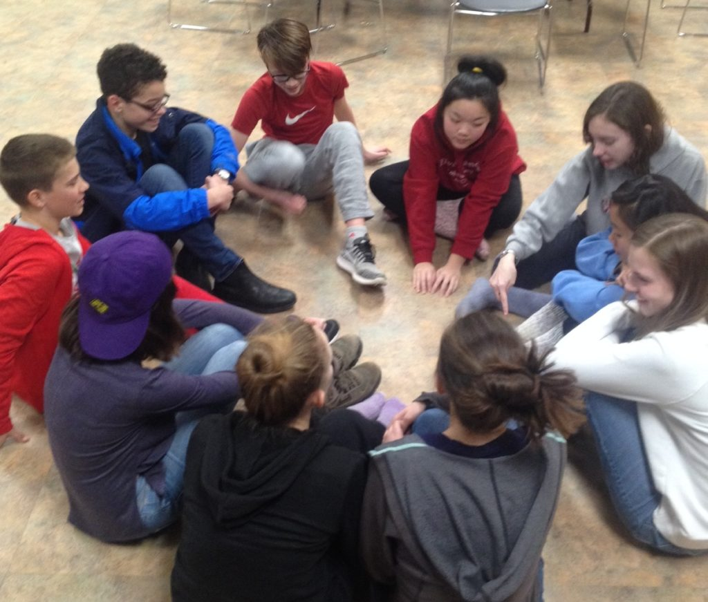 10 youth sitting on the floor in a circle