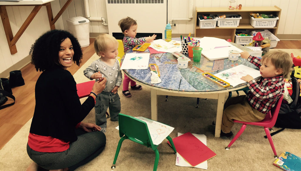 Three toddlers standing around a table painting in the nursery along with an adult volunteer