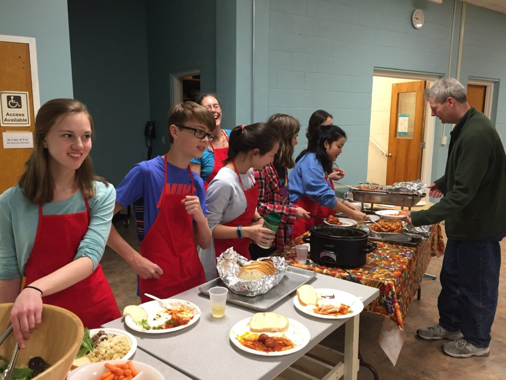 A group of youth wearing red aprons serving the meal at a pasta dinner fundraiser in the fellowship hall