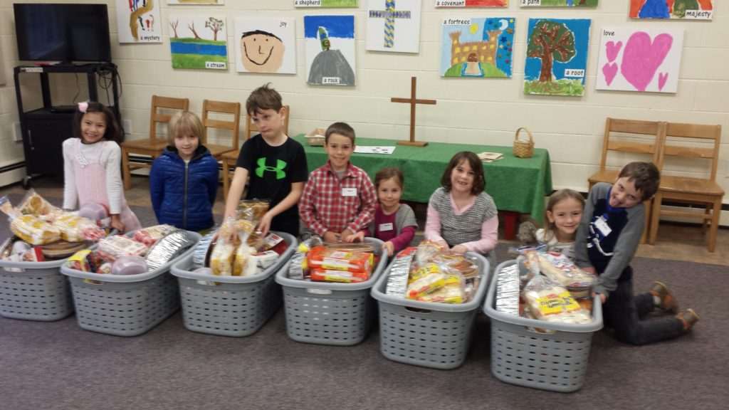 Eight youth sitting behind laundry baskets filled with food donated for Thanksgiving baskets