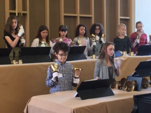 Nine members of the youth handbell choir performing with bells