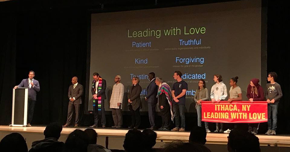 "13 community leaders, faith leaders, and students (including Mayor Myrick, Superintendent Brown, and Pastor Kaden) on a stage with a banner reading ""Ithaca, NY Leading with Love"""