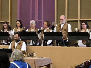 Seven members of the handbell choir wearing tan vests and performing with bells