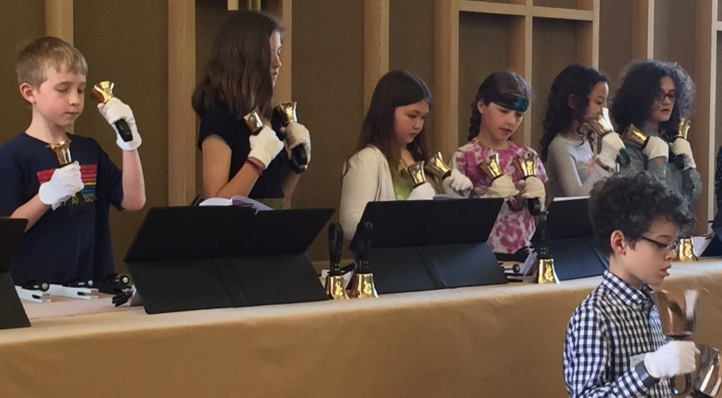Seven youth performing with handbells