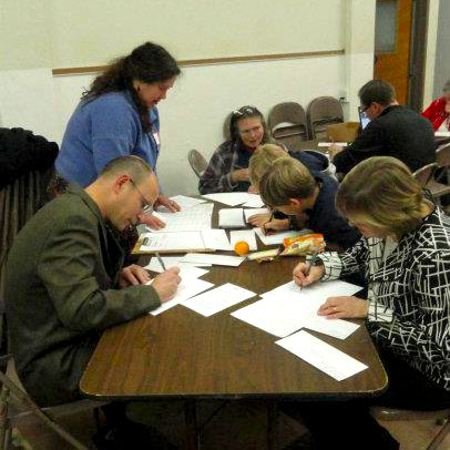 Several church members writing letters at a table
