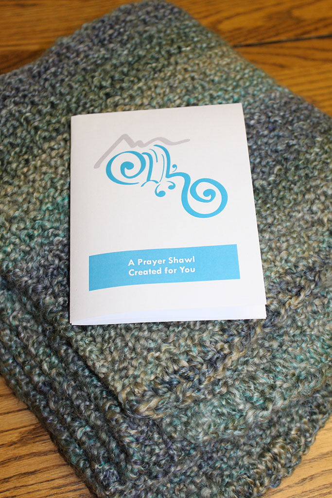 """a gray prayer shawl folded with a card reading """"A Prayer Shawl Created for You"""""""