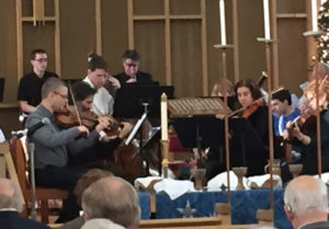 Brass and string players performing behind the altar